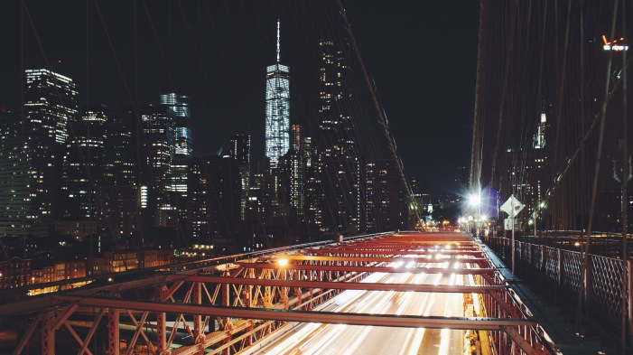 New York City skyline at night from a bridge.