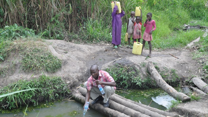 Uganda kids fill up jerry cans at a contaminated stream for their water supply.