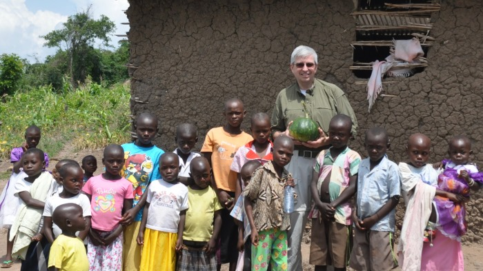 Veolia's Bill Naughton stands with Ugandan kids.