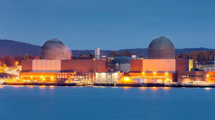 Waterfront nuclear plant with rounded towers.
