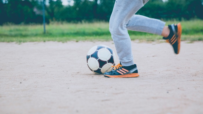 Legs of boy in Adidas shoes playing soccer.