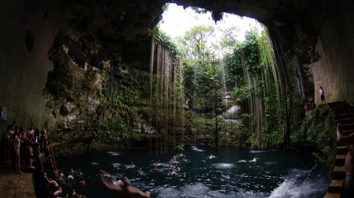People jumping into pool of water in a cenote in Mexico.