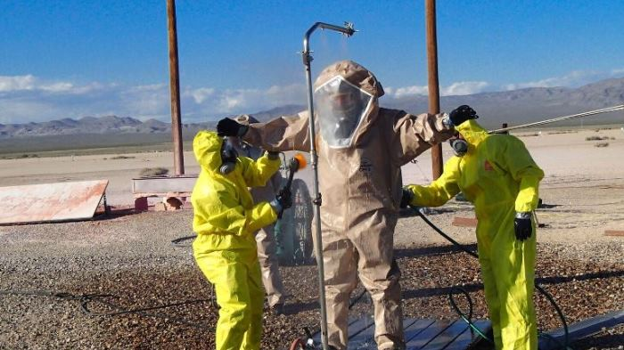 Person in hazmat suit being decontaminated in Nevada desert.