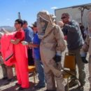 People in hazmat suits in Nevada desert.