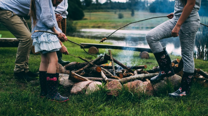 Little girls roasting hot dogs over a campfire on grass.