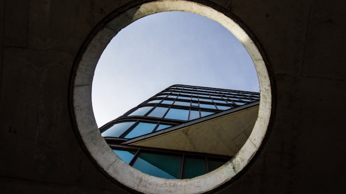 Circular window looking up at city building.